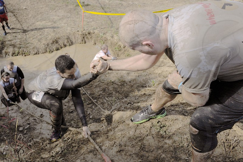 man wearing shirt with mud helping man to climb holding him tightly at daytime photo