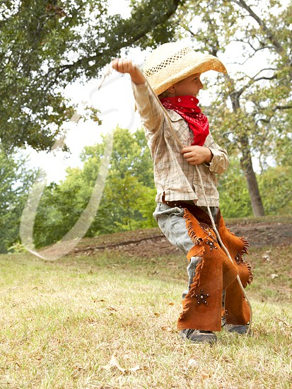 Kid playing with lasso dressed in cowboy hat and clothes. Kids playing Cowboy and Indian.  photo