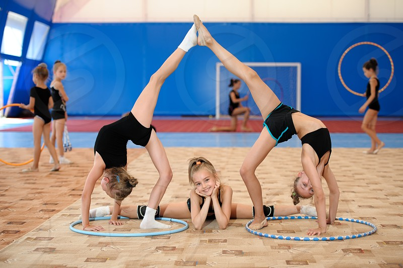Young female gymnasts posing. Girl doing leg-split between two ones stretching legs up photo