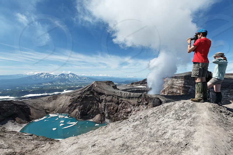 KAMCHATKA PENINSULA RUSSIA - JULY 21 2013: Group of tourists and travelers stand on top of active Gorely Volcano watching at work of volcano fumaroles erupting cloud of steam and gas from crater. photo