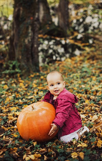 Young happy baby girl in the forest in autumn holding a big pumpkin and smiling. photo