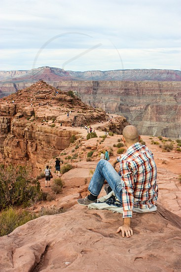 man sitting looking on grand canyon view photo