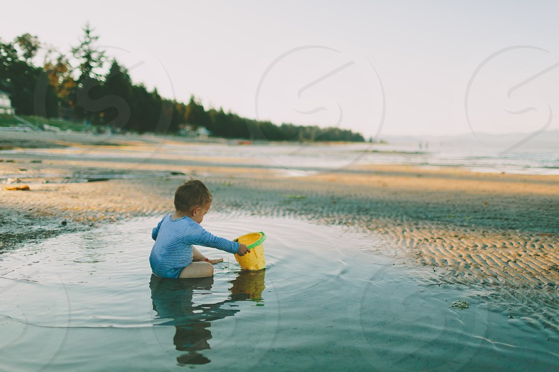 A baby boy playing in the tidal pools on the beach.  photo