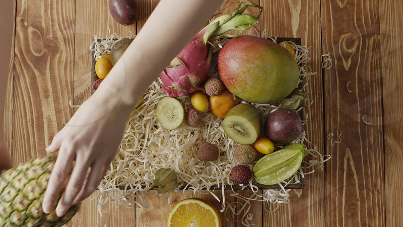 Variety tropical fruits on a wooden straw in a box on a wwoden background. Girl's hands take out ananas mango dradon fruit from the box n a table. Fast motion 4K UHD video 3840 2160p. photo