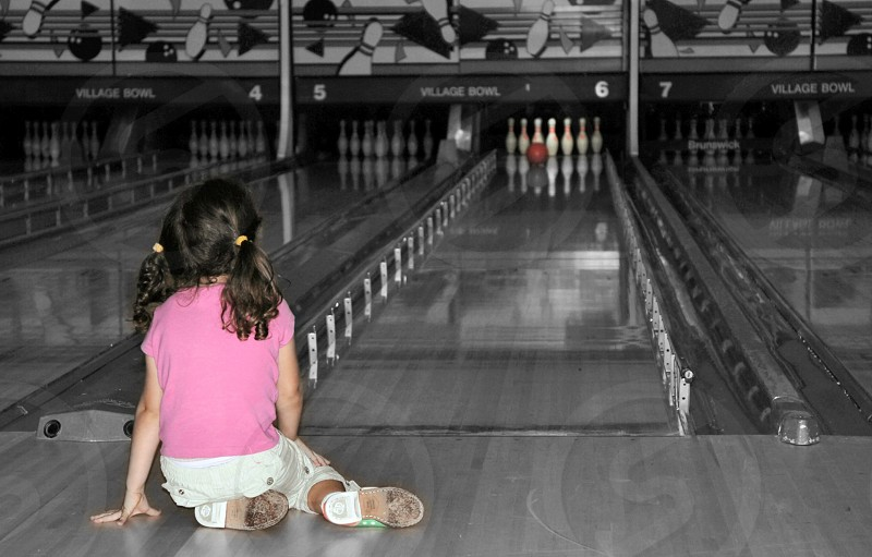 Girl sits and watches the bowling ball photo