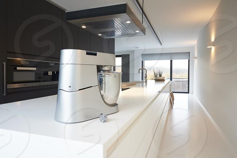 Ultra modern designer kitchen with all modern appliances in a bright white interior space photo