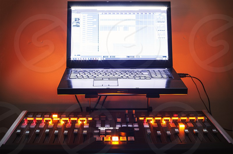 Modern mixing console and laptop on table small home recording studio.  photo