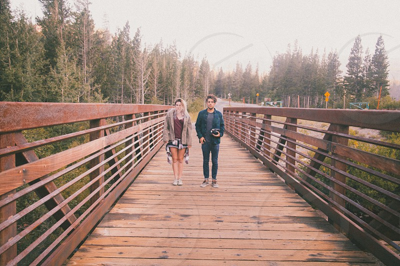 man and woman standing on the bridge photo