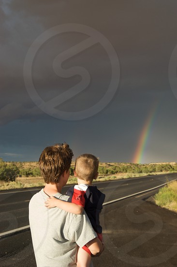 Rainbow. Mother and son. Watching rainbow.  photo