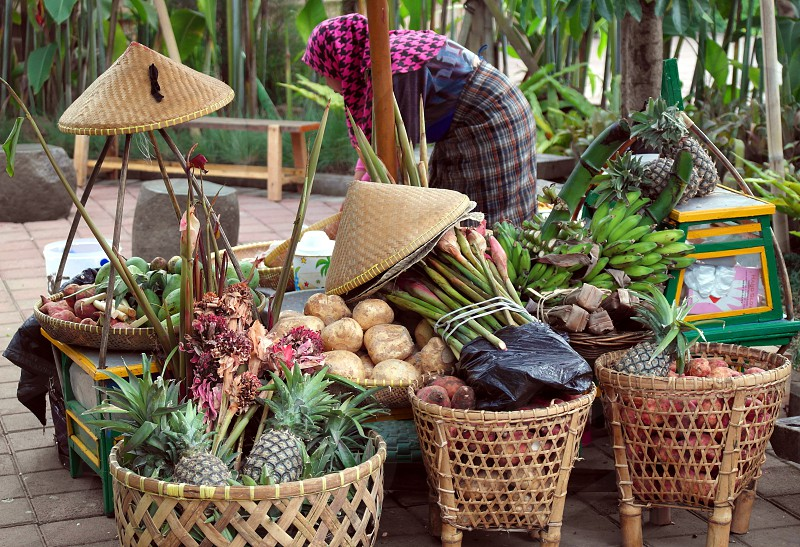 woman in pink and black hijab near fruits on brown wicker basket during daytime photo