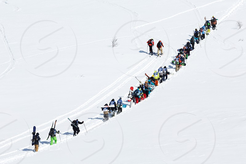 KAMCHATKA PENINSULA RUSSIA - MARCH 9 2014: Group of sportsmens - snowboarders and skiers climb the mountain for freeride. Competition Kamchatka Freeride Open Cup on Russian Far East. photo