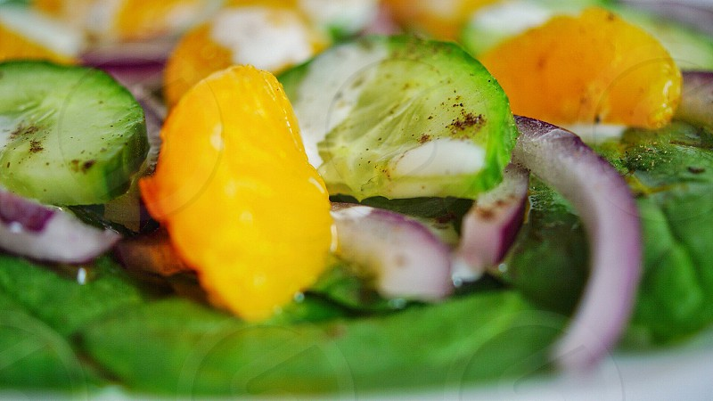 orange onion and cucumber salad in plate photo