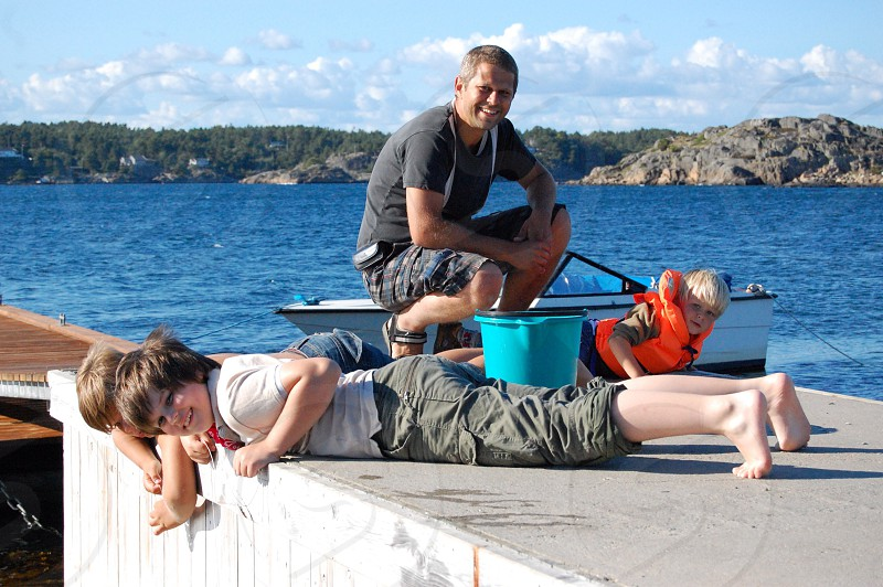 2 kids and a man lying on dock photo