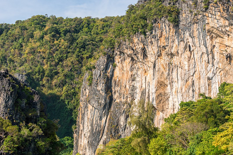 Big orange limestone cliff covered by tropical greenery photo
