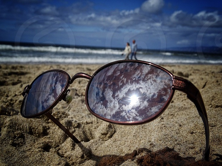 brown framed sunglasses near person during daytime photo