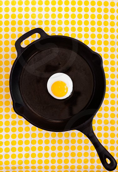 Overhead view of a single sunny side up egg in a black cast iron skillet photo