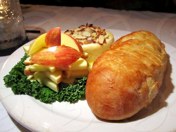 Baked brie topped with almonds with apple slices and fresh baked bread photo