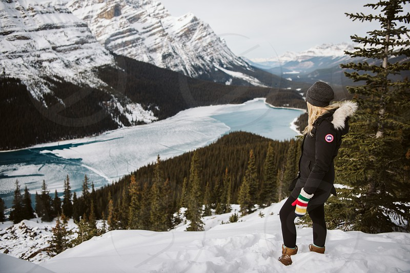 A girl standing at the top of a snow covered Bow Summit over looking Peyto Lake in Banff National Park in Alberta Canada. photo