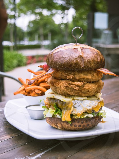 burger with crispy chicken cheese and vegetables on white ceramic plate photo