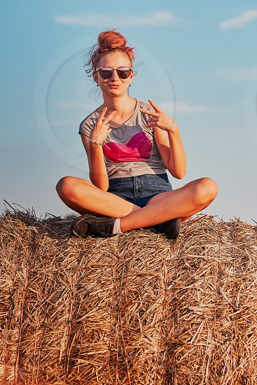 Happy smiling teenage girl sitting on a hay bale at sunset making V sign gesture enjoying summer vacations in the countryside. Candid people real moments authentic situations photo