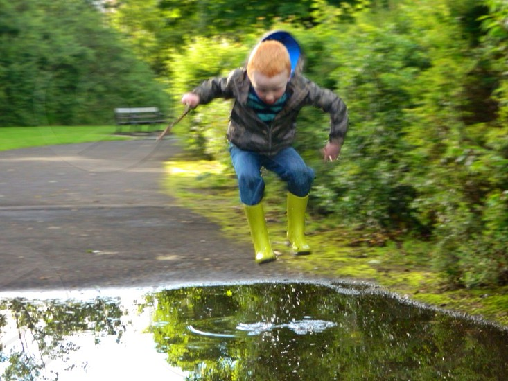 Boy puddle jump fun splashing in the rain  photo