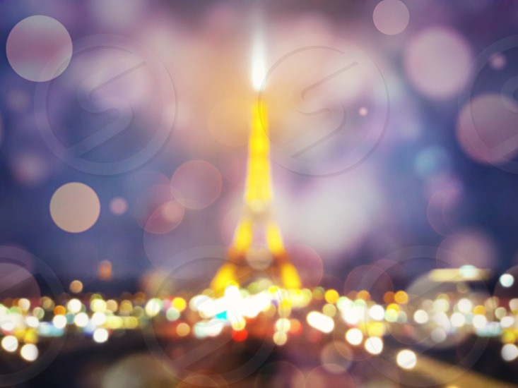 Blurred defocused night scene and Eiffel Tower silhouette shining in Paris with defocus bokeh and colorful lights. Romantic symbol background. photo