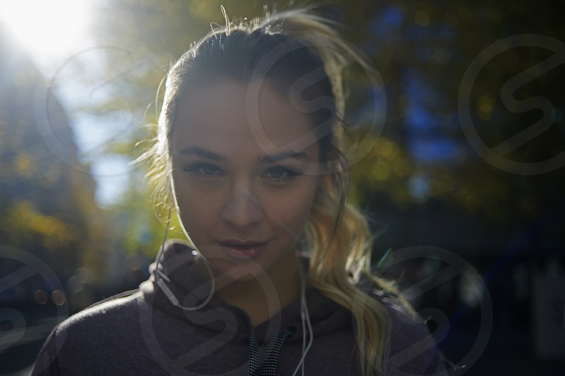 Attractive young caucasian woman wearing a hood exercising and running outside in the city centre in autumn sunshine with long shadows photo