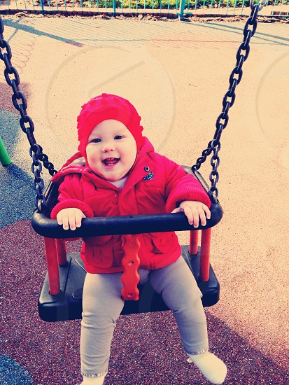 Baby girl swing laugh smile fun park autumn winter photo