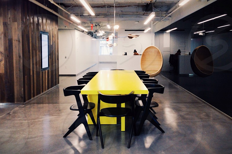 long yellow table with black wood chairs photo