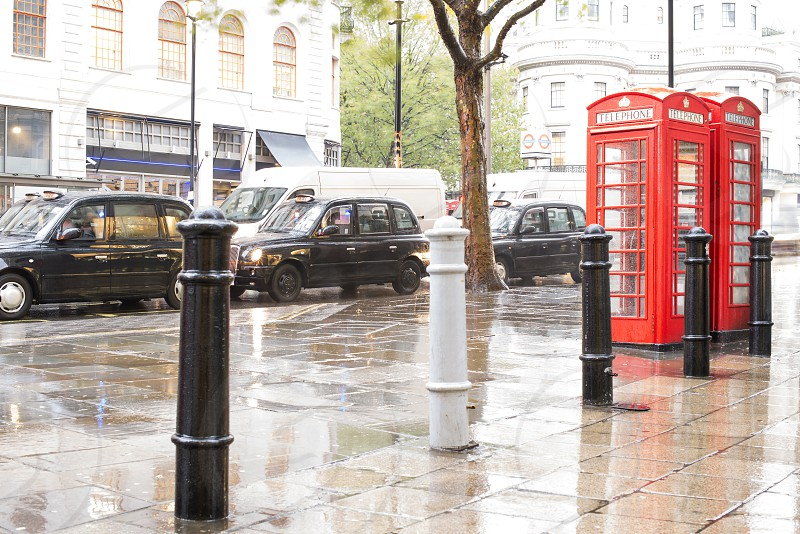 Red Phone cabines in London and vintage taxi.Rainy day. Vintage phone cabine monumental photo