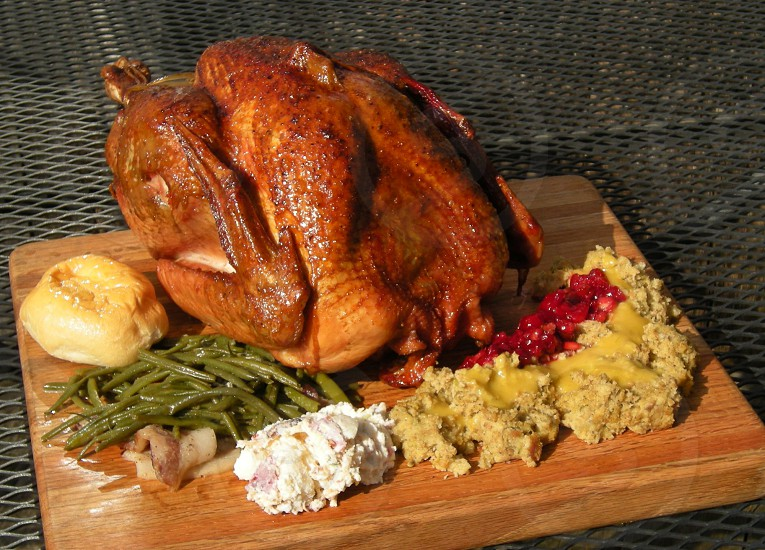 Turkey dinner with smoked turkey dressing cranberries gravy green beans potato salad roll on wood background landscape version photo