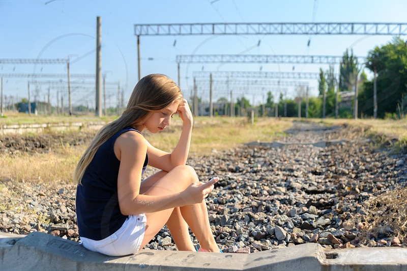 Girl teenager in top and shorts using cellphone while sitting on concrete of unfinished rail track in the countryside photo