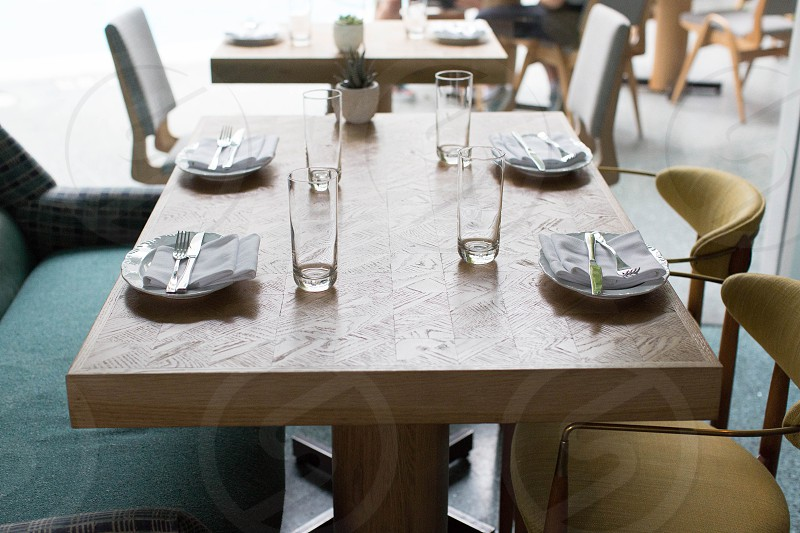 brown wooden rectangular table with clear glass cup plates and stainless fork and butter knife with brown chairs during daytime photo