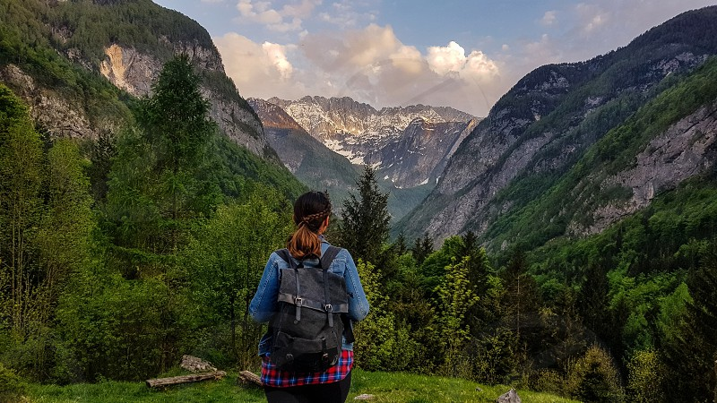 Lone female hiker with a backpack admiring the view in the mountains. photo