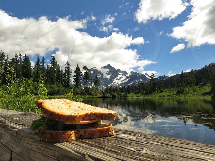 Famous Picture Lake Mt Baker WA picnic sandwich travel destination dock water trees mountain summer reflections blue sky clouds landscape view snow capped mountains. photo