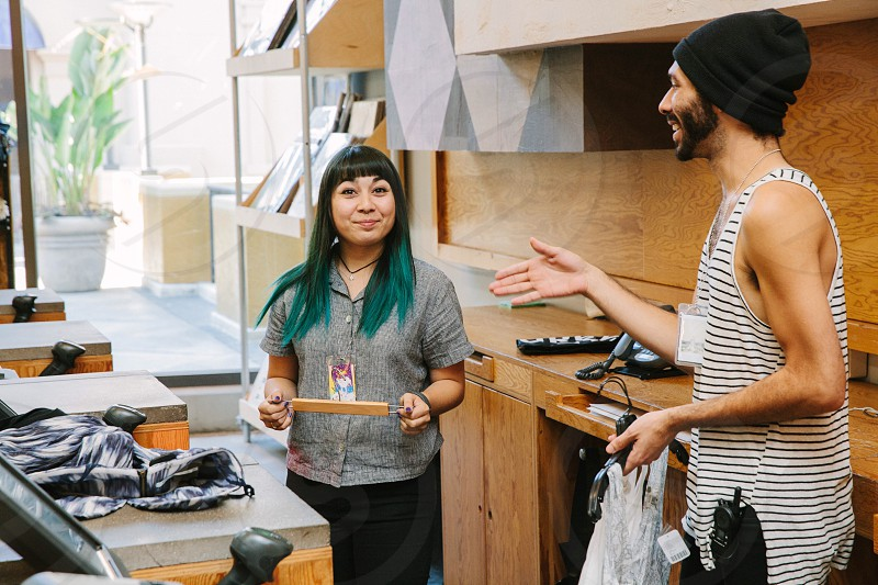 man in black knit cap offering a hand shake to woman in gray button up shirt photo