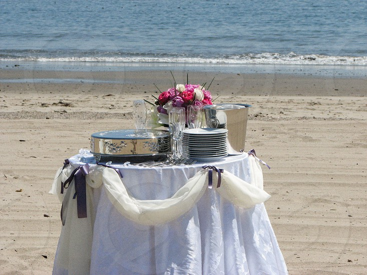 Table with flowers dishes and a silver platter on the beach. photo