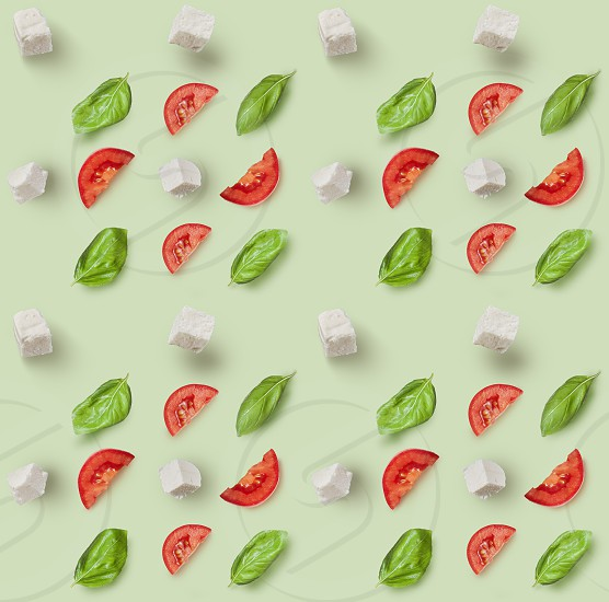 Seamless pattern mozzarella cherry tomatoes and fresh basil. Ingredients for caprese salad on a green background photo