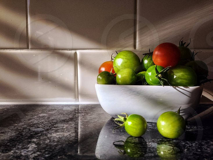 green and red tomatoes in white ceramic bowl photo