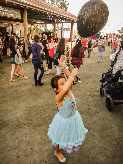 little girl with a balloon at a fair photo