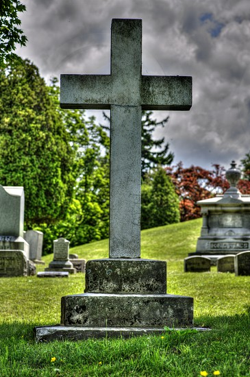 Beautiful cross tombstone in a grassy area and nice clouds. photo