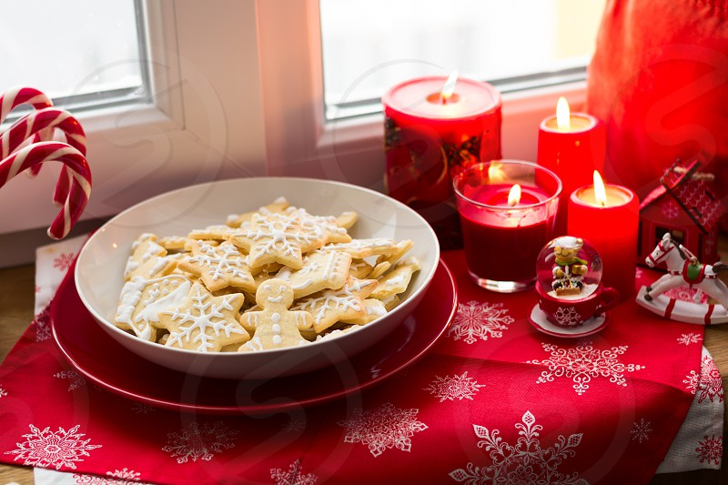 Christmas decoration: gingerbread cookies candies toys and burning red candles on windowsill photo