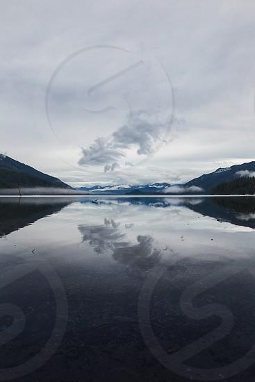lake mountains clouds reflection still water winter monochromatic photo