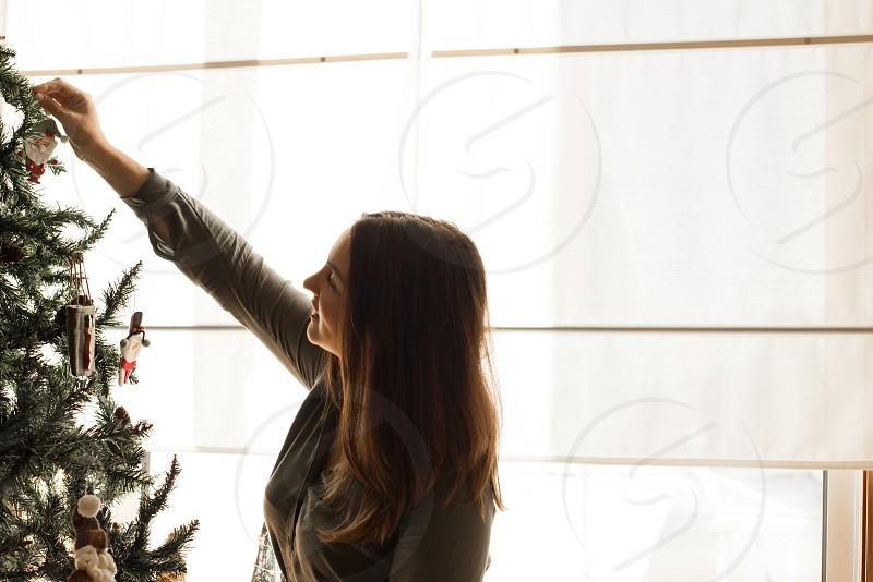 Woman decorating Christmas tree at home photo