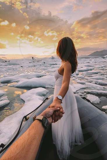 woman wearing white spaghetti strap dress holding man's hand surrounded by icebergs during sunset photo
