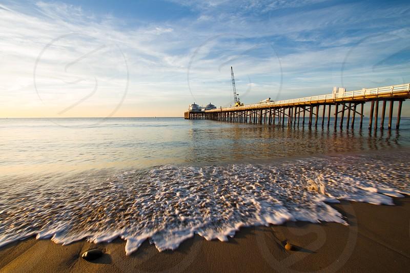 Malibu pier landscape ocean California beach water sand sunrise blue skies clouds photo