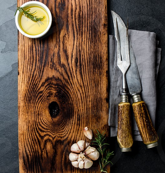 Cooking background concept. Vintage cutting board cutlery and spices. Top view photo