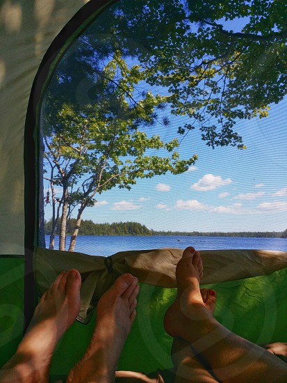 Camping in the backyard for a summer staycation. The view is from the inside of the tent looking out through the screen door from the bed. Feet are in view to add a sense of fun. Blue skies a lake an island and trees. Natural fun. photo