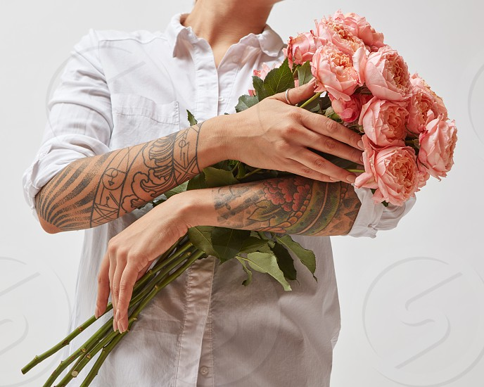 Happy girl with a tattoo on her hands holding a bouquet of pink media roses mother's day valentine's day photo