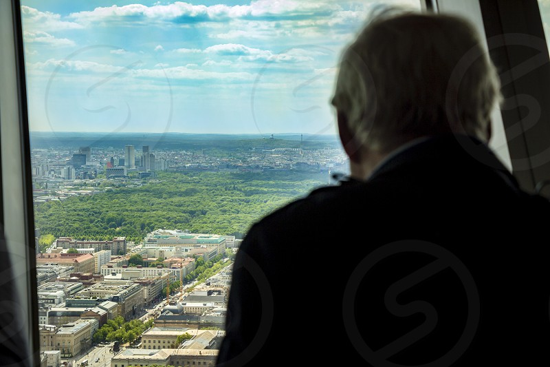 Silhouette of back view of man looking out of a window at the berlin city skyline. photo